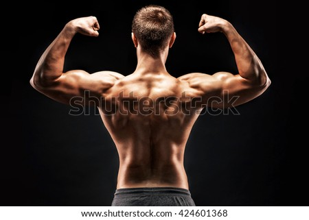 Rear view of muscular young man showing back, biceps muscles - stock photo