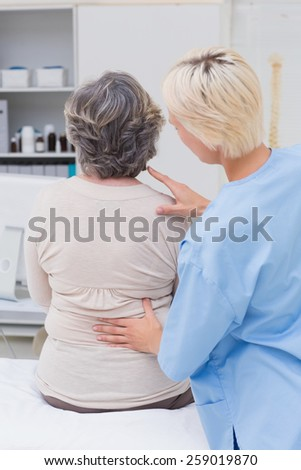 Rear view of nurse examining female patients back in clinic - stock photo