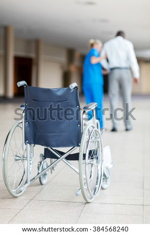 rear view of nurse helping patient walk with wheelchair in foreground  - stock photo