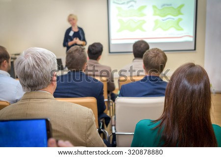 Rear View of Office Employees in a Business Meeting Inside the Office, Listening to Woman Presenting Something.