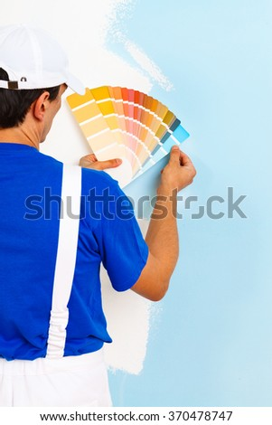 rear view of painter man looking a color palette on half painted wall, with copy space