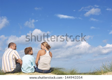 Rear view of parents and son sitting on sand and looking at eachother on beach - stock photo