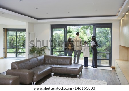 Rear view of parents with daughter and female estate agent at new property - stock photo