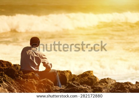 Rear  view of pensive, depressed man sitting on coast rock, looking at sea horizon.Copy space, unrecognizable person, lens flare, sunset light - stock photo