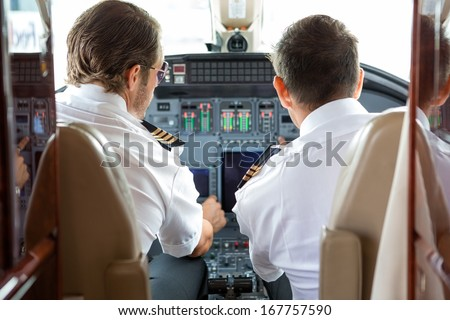 Rear view of pilot and copilot in private jet cockpit - stock photo