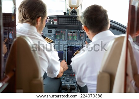 Rear view of pilot and copilot operating controls of corporate jet - stock photo