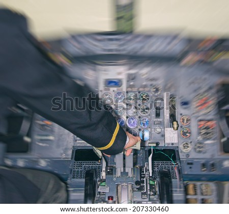Rear view of pilot in aircraft cabin. Motion effect. - stock photo