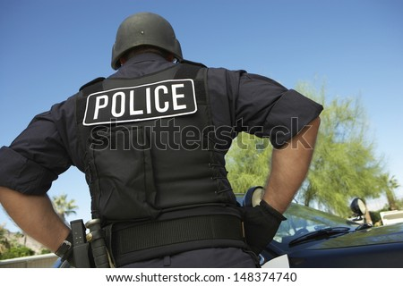 Rear view of policeman in uniform standing against car - stock photo