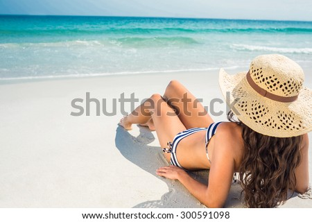 Rear view of pretty brunette looking at the ocean on a sunny day - stock photo