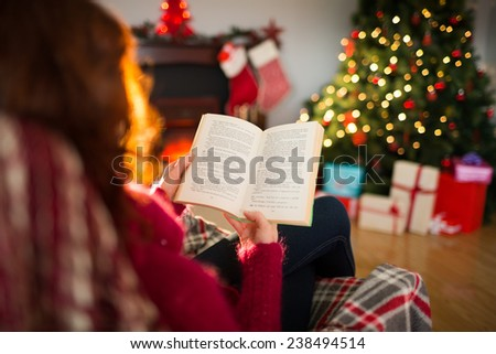 Rear view of redhead reading at christmas at home in the living room - stock photo