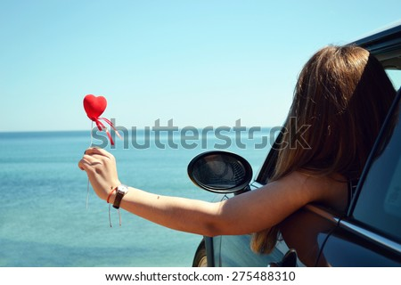 Rear view of relaxed woman on summer travel vacation to the coast leaning out car windows  towards the sea, - stock photo