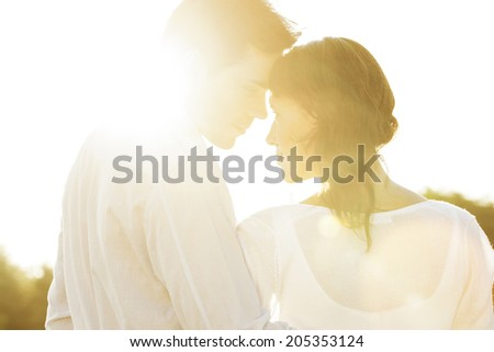 Rear view of romantic couple looking at each other during summer - stock photo