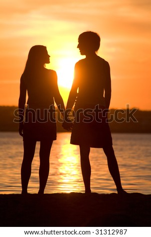 Rear view of romantic couple looking at each other on seashore at sunset - stock photo