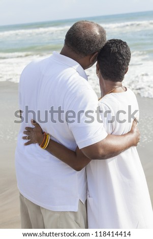 Rear view of romantic senior African American man and woman couple on a deserted tropical beach - stock photo