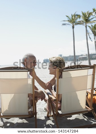 Rear view of romantic senior couple sitting on deckchairs at sunny beach - stock photo