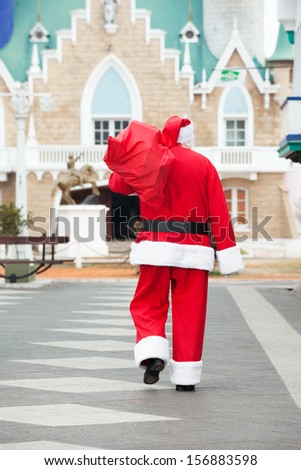 Rear view of Santa Claus carrying bag while walking in courtyard - stock photo
