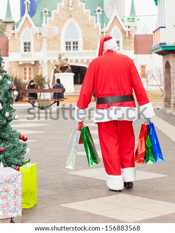Rear view of Santa Claus with bags walking in courtyard - stock photo