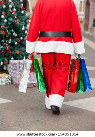 Rear view of Santa Claus with shopping bags walking in courtyard - stock photo