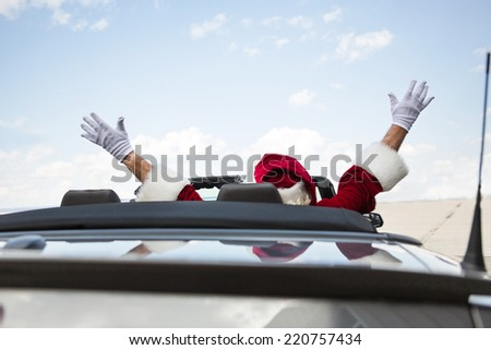 Rear view of Santa with arms raised in convertible - stock photo