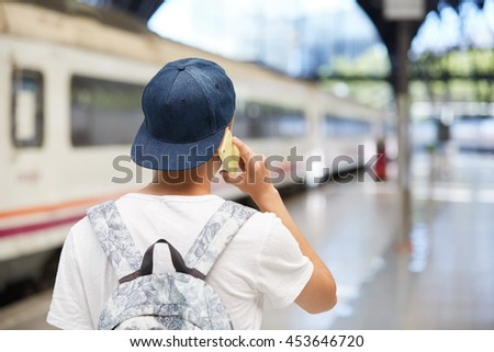 Rear view of schoolboy in street wear talking on mobile phone, discussing plans for summer vacations with his friends while walking home from school wearing snapback backwards. Selective focus - stock photo