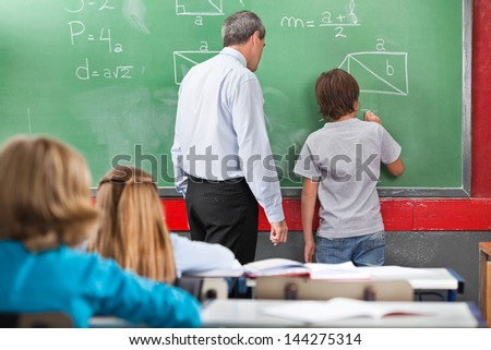 Rear view of schoolboy solving mathematics on board with teacher in classroom - stock photo