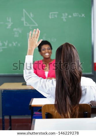 Rear view of schoolgirl raising hand with female teacher in background at classroom