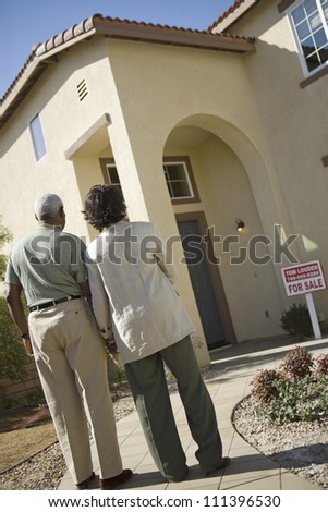Rear view of senior African American couple in front of house for sale - stock photo