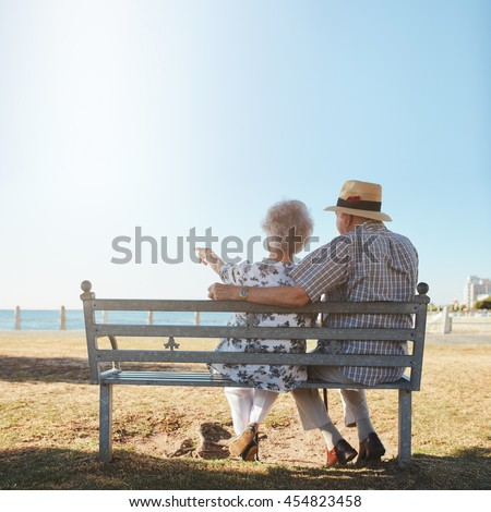 Rear view of senior couple relaxing on a bench with woman pointing out to sea. Retired man and woman sitting on a bench outdoors and enjoying the view. - stock photo