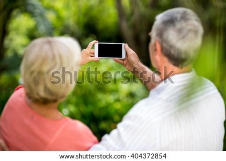Rear view of senior couple taking selfie in yard - stock photo