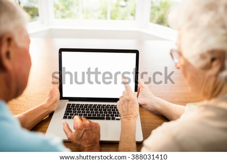 Rear view of senior couple using laptop at home - stock photo