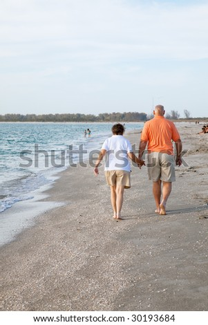 Rear view of senior couple walking on the beach.