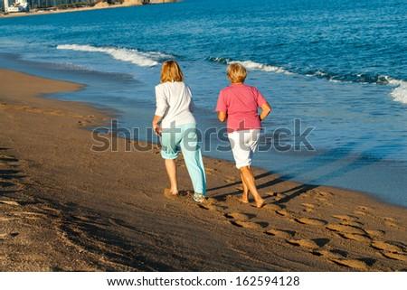 Rear view of senior women jogging on beach. - stock photo