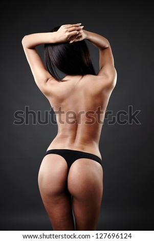 Rear view of sensual Arab woman dancing over gray background - stock photo