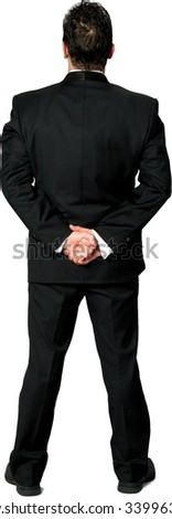 Rear view of Serious Caucasian man with short black hair in a tuxedo with hands behind back - Isolated - stock photo
