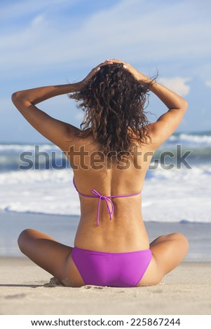 Rear view of sexy young brunette woman or girl wearing a bikini sitting on a deserted tropical beach with a blue sky  - stock photo
