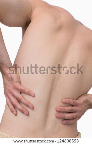 Rear view of shirtless man with back pain over white background