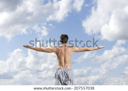 Rear view of shirtless young man standing arms outstretched against cloudy sky - stock photo