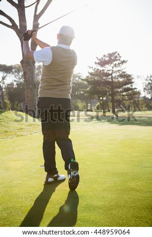 Rear view of sportsman playing golf on a field - stock photo