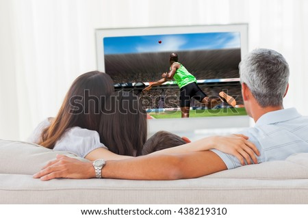 Rear view of sportsman throwing a shot against family watching television together on sofa - stock photo