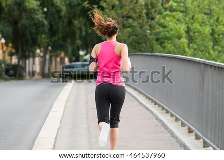 Rear View Of Sporty Young Woman Running On Sidewalk In Morning