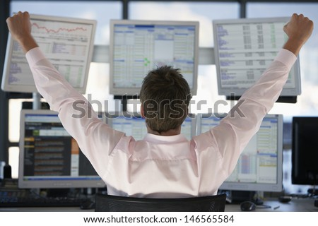 Rear view of stock trader with hands raised looking at multiple computer screens - stock photo