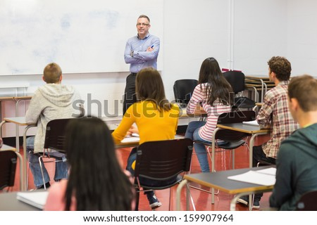 Rear view of students attentively listening to male teacher in the classroom - stock photo