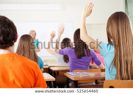 Rear view of students in bright classroom responding to the teacher's question, raising their arms up.