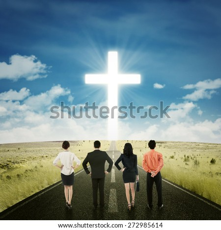Rear view of successful businesspeople standing on the road while looking at a cross
