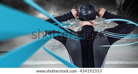 Rear view of swimmer in wetsuit wearing swimming goggles against rock crashing down from cliff