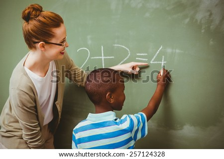 Rear view of teacher assisting little boy to write on blackboard in the classroom