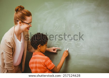 Rear view of teacher assisting little boy to write on blackboard in the classroom - stock photo