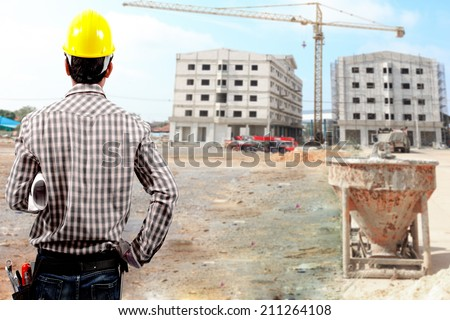 rear view of technician builder in protective safety equipment  hard hat and and blueprints at the front of blurred construction site - stock photo