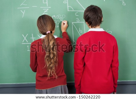 Rear view of teenage girl writing on board with classmate standing in classroom