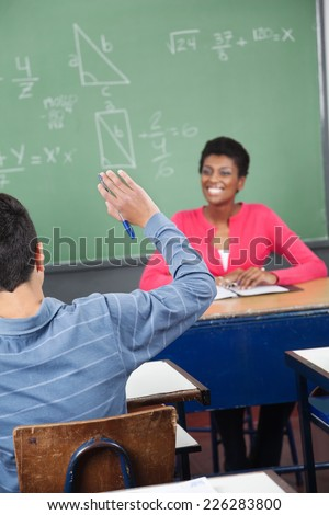 Rear view of teenage schoolboy raising hand while teacher looking at him in classroom